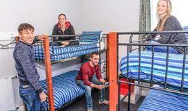 YHA Christchurch youth travelers relaxing in multishare bunk bedroom