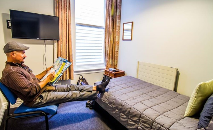 YHA Christchurch youth traveler planning in single bedroom with TV