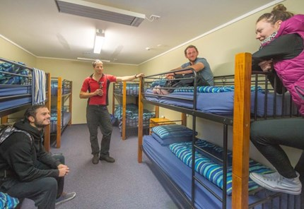 YHA Franz Josef youth travelers conversing in multishare bunkbed