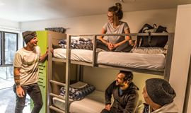 YHA Queenstown Lakefront youth travelers socialising in multishare bunkbed