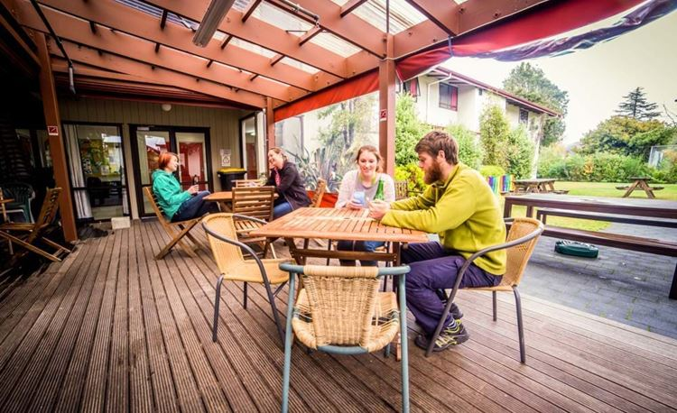 YHA Te Anau youth travelers sharing drinks in outdoor deck area