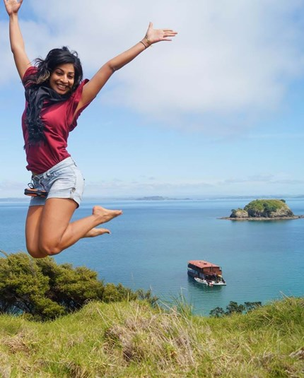 YHA Bay of Islands the Rock youth traveller jumping for joy in front of cruise