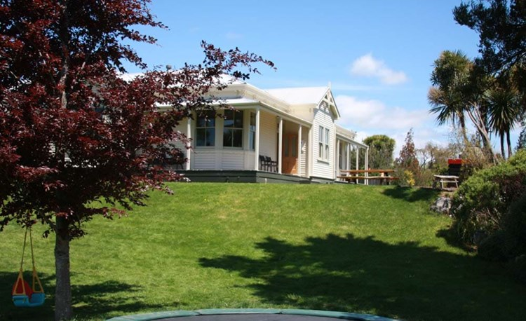 YHA Ohakune backyard with trampoline and swing with hostel exterior