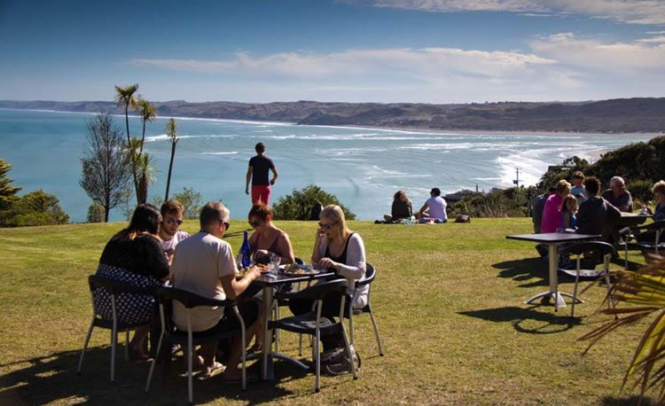 YHA Raglan youth travelers dining and socialising with ocean view