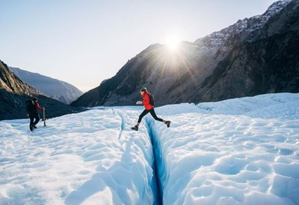 YHA Franz Josef traveller jumping over glacier creek