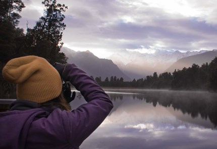 YHA Franz Josef traveller taking photos over lake matheson