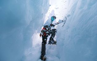 climber with pick axe and campons heading into crevasse