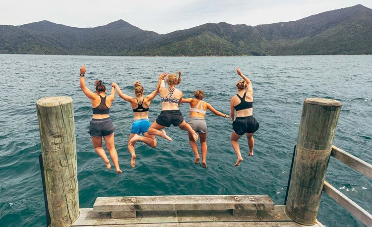Girls jumping off from jetty