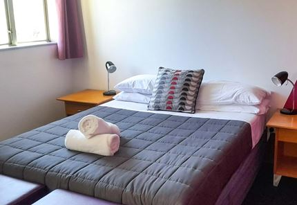Double room at YHA Nelson set up for couples with double bed and towels.
